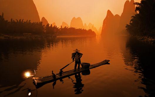 Обои Рыбак в широкополой шляпе рыбачит на лодке с фонарем на фоне заката