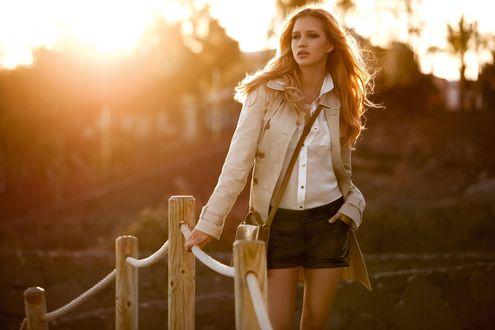 Обои Светловолосая девушка в белой блузке, шортах и плаще стоит на фоне природы