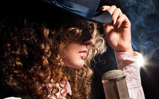 Обои Кудрявая рыжеволосая девушкав шляпке с микрофоном