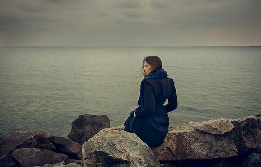 Обои Девушка в пальто сидит на камнях у моря, фотограф Valeriya Tikhonova