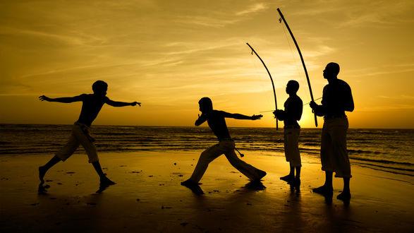Обои Мужчины занимаются капоэйрой на берегу моря на фоне заходящего солнца, Brazil Capoeira