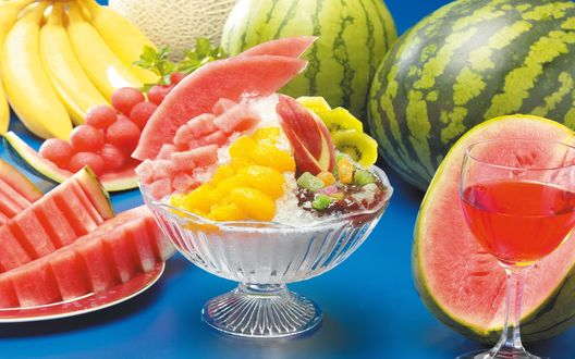 Обои Фруктово- ягодный микс в креманке со льдом, бокал с соком, арбузы, виноград и бананы на столе