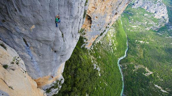 Обои Туристка, взбирающаяся на отвесную скалу, на фоне гор и долины, покрытых зеленью