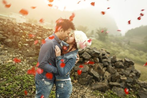 Обои Влюбенная пара обнявшись улыбаются друг другу на фоне природы в окружении летающих лепестков цветов