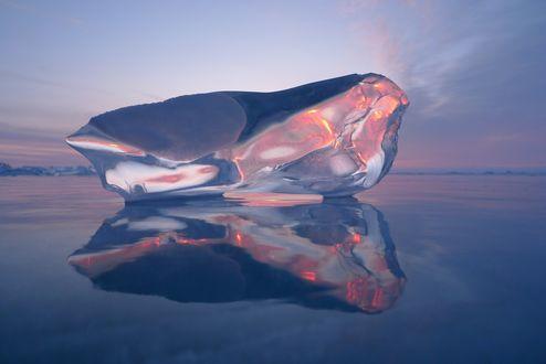 Обои Большая глыба льда просвечивается в лучах солнечного заката