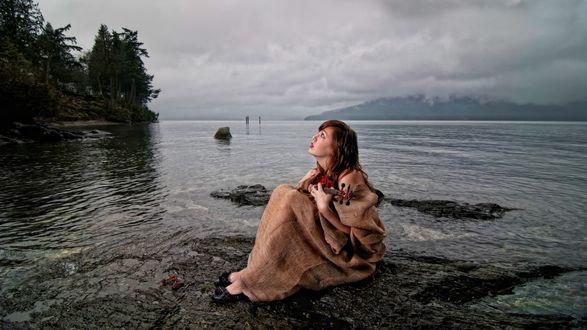 Обои Девушка, завернутая в накидку, со скрипкой в руках сидит на камне на берегу водоема на фоне размытых дождевых туч