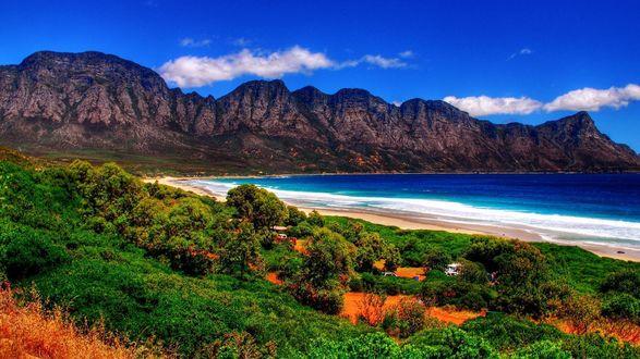 Обои Морское побережье на фоне скал и голубого неба с облаками