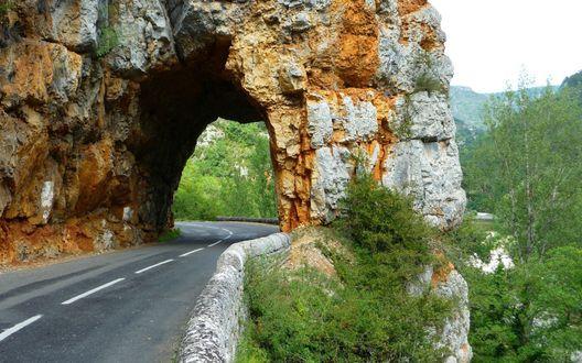 Обои Асфальтовая дорога через тоннель в скале на фоне гор и деревьев