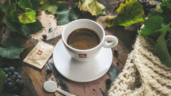 Обои Чашка кофе стоит на столе, рядом с виноградными гроздьями и листьями
