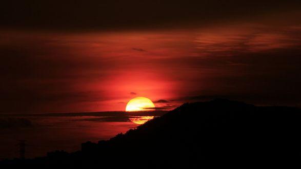 Обои Солнце заходит, опускаясь в воду на горизонте, закат в красно-черных тонах
