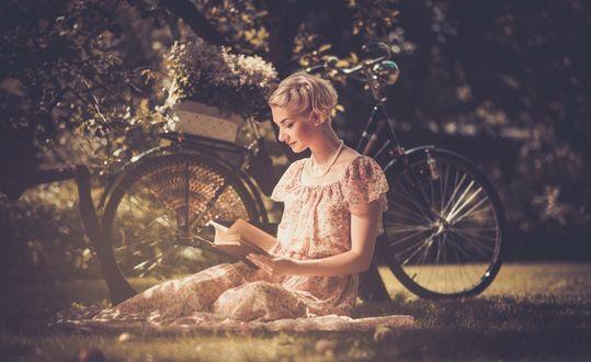 Обои Девушка сидит на лужайке возле велосипеда и читает книгу на темном размытом фоне