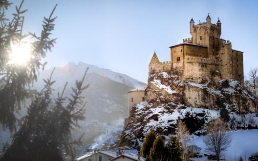 Обои Заснеженный старинный Castello di Saint-Pierre, Italy / замок Сен-Пьер, Италия на скале на фоне пробивающегося солнца и размытых очертаний гор