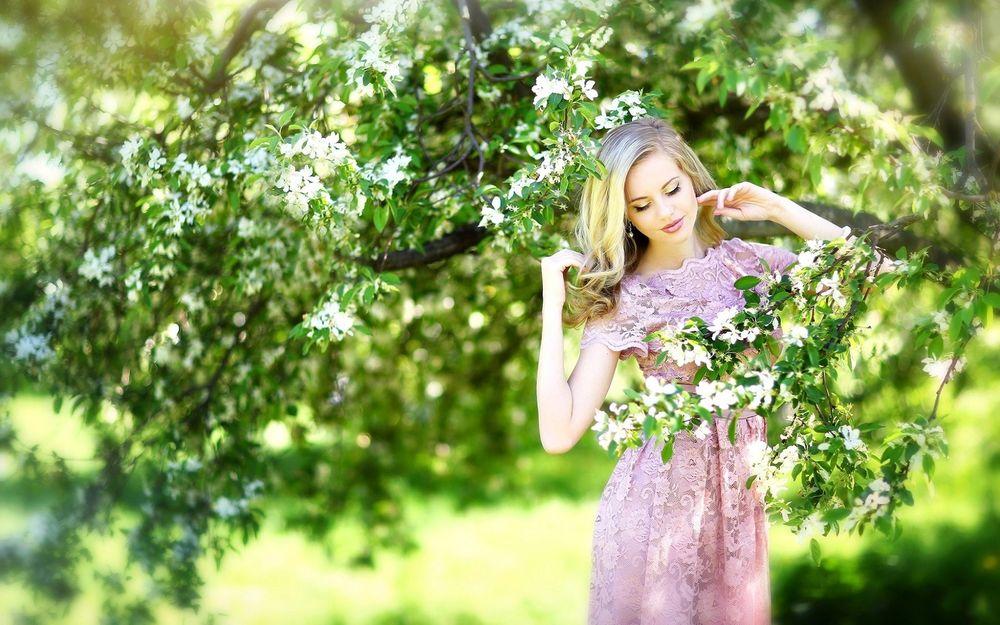 Обои для рабочего стола Красивая блондинка в розово-сиреневом платье стоит среди цветущих весенних деревьев