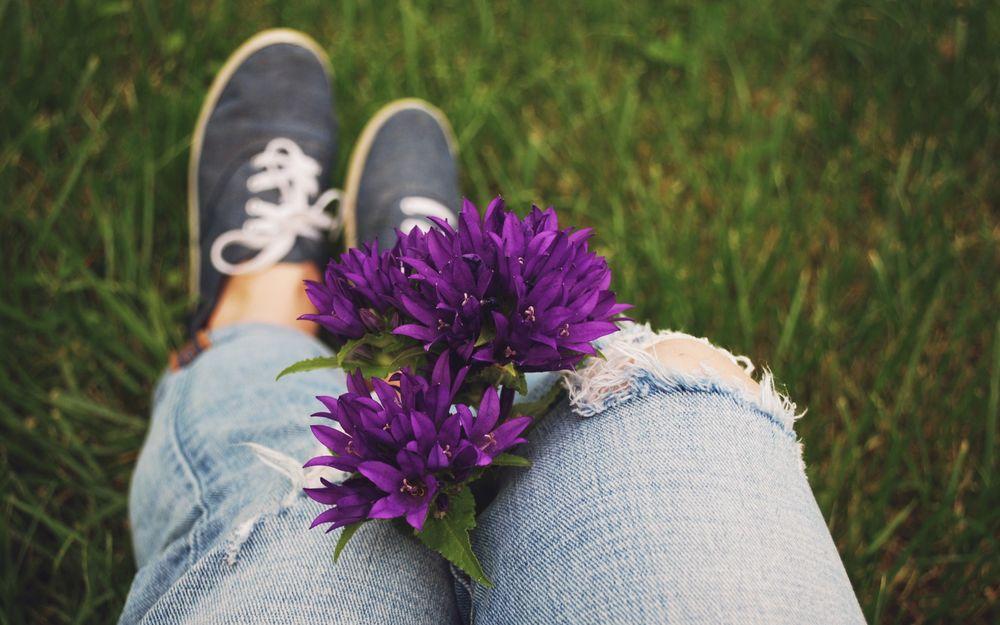Обои для рабочего стола Букет фиолетовых цветов в ногах у девушки