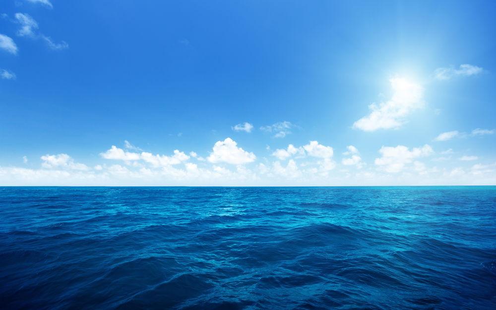 Обои для рабочего стола Бескрайний океан на фоне синего облачного неба