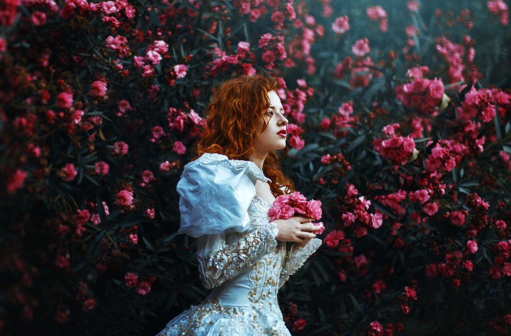Обои для рабочего стола Рыжеволосая девушка стоит у куста цветов, фотограф Ronny Garcia