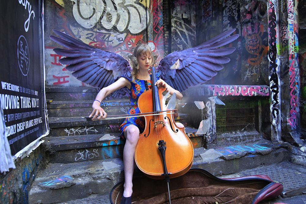 Обои для рабочего стола Девушка - ангел играет на виолончели, чтобы заработать деньги на еду