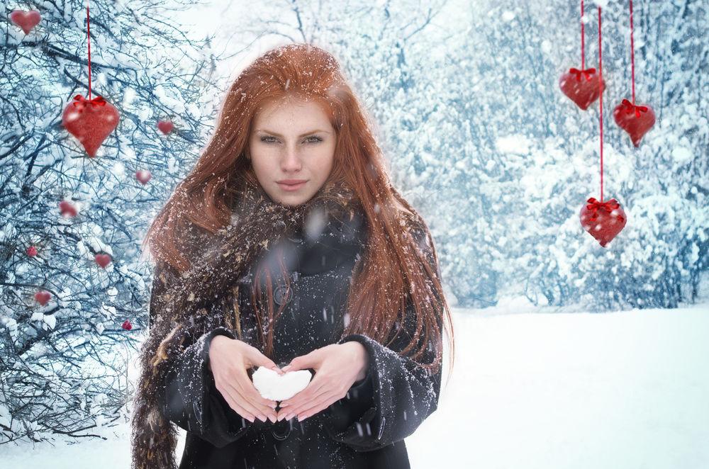 Обои для рабочего стола Рыжеволосая девушка на зимнем фоне под падающим снегом и свисающими сверху сердечками. Фотограф Таня Маркова