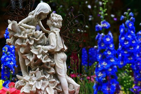Обои Статуи мальчика и девочки стоят в цветущем саду