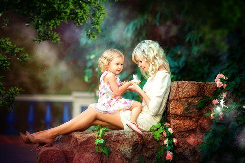 Обои Мама с дочкой сидят на камнях в парке и держат на ладонях маленькую фею
