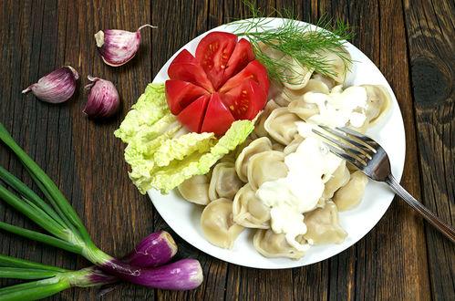 Обои Тарелка с пельменями со сметаной, овощами и зеленью стоит на деревянной поверхности