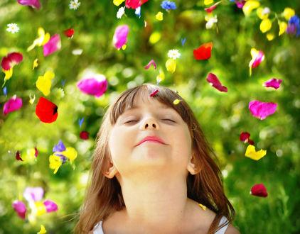 Обои Девочка с закрытыми глазами, подняв голову вверх стоит под падающими на нее лепестками цветов