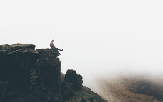 Обои Мужчина сидит на краю скального выступа и болтает ногами, под ним расстилается туман