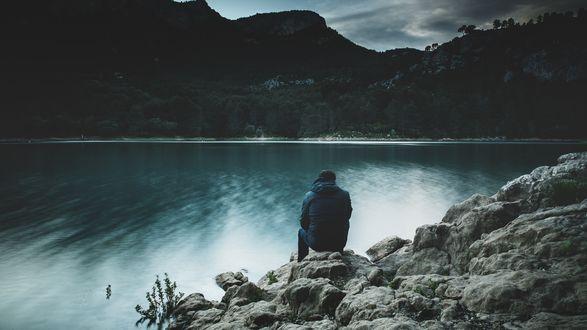Обои Парень сидит на каменистом берегу озера