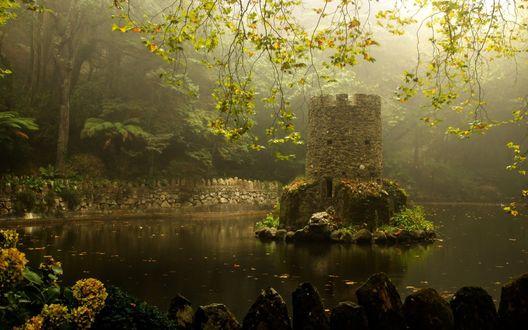 Обои Каменная башенка на небольшом островке посреди водоема, окруженного густыми деревьями на фоне сгущающегося тумана