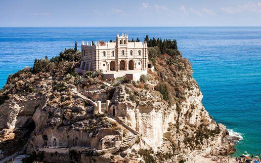 Обои Дом-крепость на скалистом острове, освещенный летним солнцем на фоне лазурного моря и голубого неба