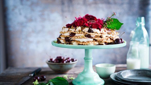 Обои Десерт с вишней в вазе, рядом миска с ягодой, две бутылки молока и листья