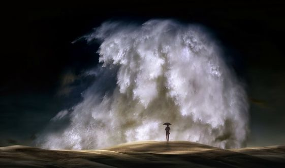 Обои Мужчина с зонтом стоит на фоне огромной волны, фотограф nikos Bantouvakis