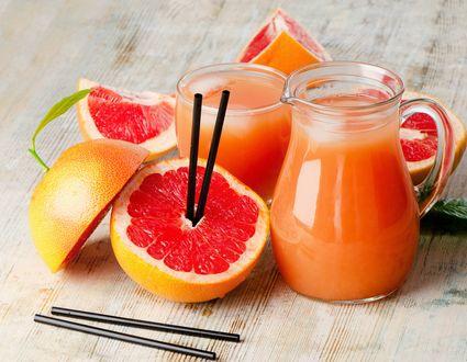 Обои Кувшин со свежевыжатым соком грейпфрута рядом разрезанные плоды и соломинки