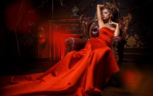 Обои Девушка в огненно-красном платье сидит в отблесках красного света на фоне полутемной комнаты