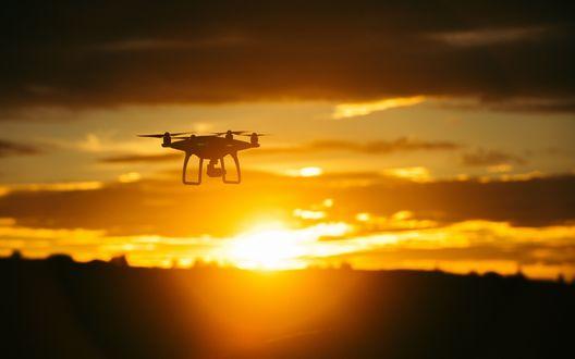 Обои Квадрокоптер летит на фоне закатного неба над размытым горизонтом