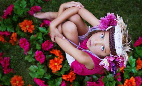 Обои Голубоглазая светловолосая девочка с цветами в волосах сидит босиком среди садовых цветов и смотрит вверх на фотографа