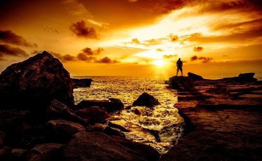 Обои Мужчина стоит на краю каменного уступа над морем, на фоне заката