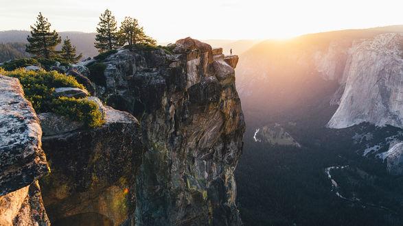 Обои Турист на краю скалы возвышающейся над горами