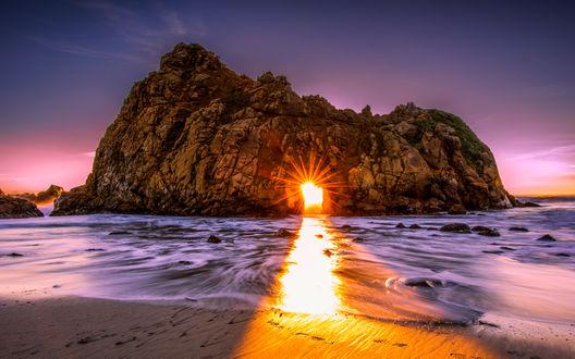 Обои Лучи заходящего солнца проглядывают сквозь дыру в морской скале