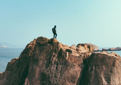 Обои Мужчина стоит на вершине скалы, возвышающейся над морем