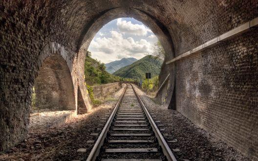 Обои Железнодорожный туннель в горном массиве, из него виднеются горы на фоне белых туч