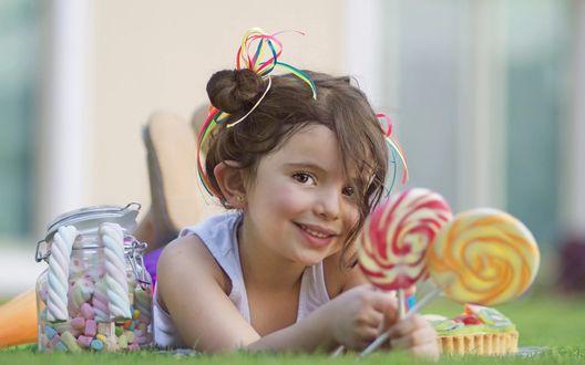 Обои Улыбающаяся девочка со сладостями в банке и с леденцами в руке лежит на траве