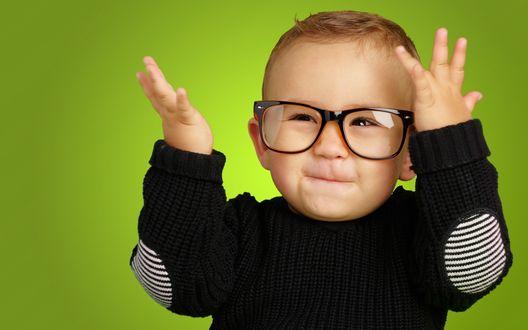Обои Смешной мальчик в очках с поднятыми руками на зеленом фоне