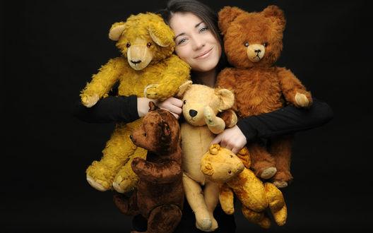 Обои Улыбающаяся девушка с разноцветными игрушечными медведями