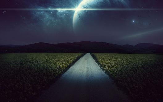 Обои Ночная дорога посреди поля с посадками на фоне гор и фантастического неба