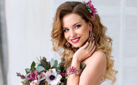 Обои Улыбающаяся светловолосая девушка с обнаженной спиной, цветком в волосах и букетом в руках стоит вполоборота к камере