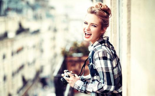 Обои Улыбающаяся светловолосая девушка с собранными в прическу волосами, в клетчатой рубашке, с камерой в руках, на фоне размытой улицы