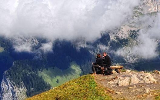 Обои Парочка туристов сидит на скамейке на уступе горы с видом на вершину горы Männlichen, Swiss Alps / Меннлихен, Швейцарские Альпы, которая скрывается в клубящемся белом тумане