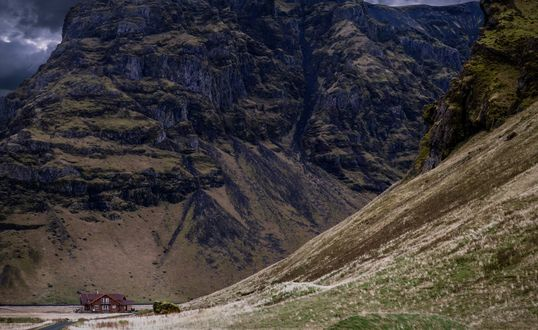 Обои Домик, притаившийся у подножья высоких скалистых гор на фоне неба, затянутого темными тучами