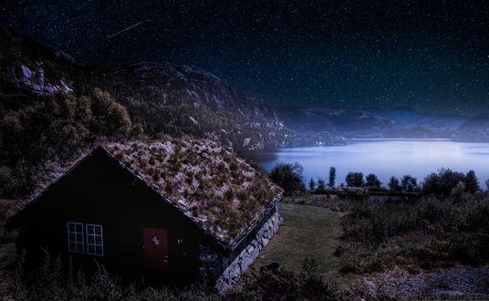 Обои Домик с красной дверью и поросшей травой крышей у ската горы на фоне гор, затянутого льдом водоема и падающего снега в лучах лунного света